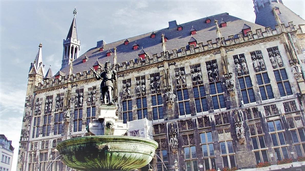In Aachen schaut er auf dem Brunnen vor dem Rathaus Richtung Norden.